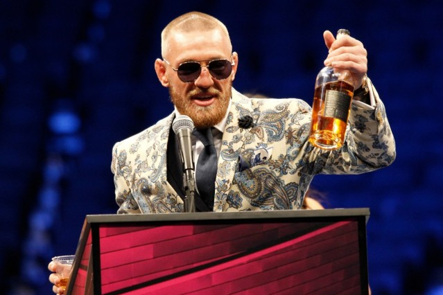 Conor McGregor addresses the media with a bottle of his Notorious Whiskey during the post-fight media conference of his
