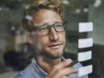 Casual young businessman with adhesive notes behind windowpane in office model released Symbolfoto PUBLICATIONxINxGERxSU
