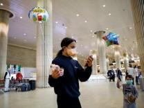 Children hold balloons in the arrivals terminal at Ben Gurion International airport in Lod, near Tel Aviv