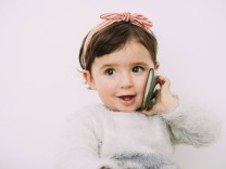 Portrait of smiling baby girl looking at cell phone model released Symbolfoto PUBLICATIONxINxGERxSUI