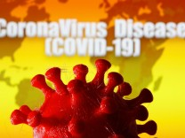 A 3D-printed coronavirus model is seen in front of a world map and the words 'CoronaVirus Disease (Covid-19)' on display in this illustration