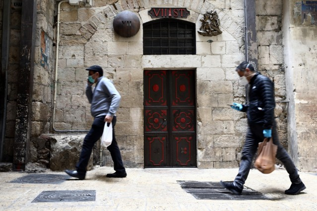 People wearing masks walk past a bronze sculpture by Italian artist Alessandro Mutto at one of the Stations of the Cross along the Via Dolorosa, amid the coronavirus disease (COVID-19) outbreak in Jerusalem's Old City