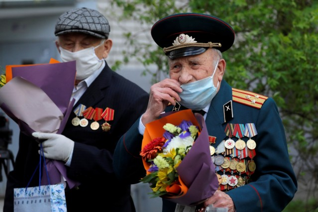 Belarusian veterans Vorobyov and Eroshenko cover their faces with protective masks as they listen to a military band outside their apartments in Minsk