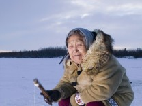 Elder Native Yupik Female Sits On Stump Ice Fishing Kuskokwim River Tuluksak Western Alaska Winter P