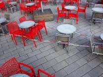 Leere rote Stühle und leere Tische vor einem Cafe - Cafe ohne Besucher - Eisdiele ohne Besucher - Corona-Krise - Virus -