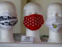 Protective masks showing a traditional design, Swiss crosses and the logo of the Swiss People's Party are displayed in Zurich