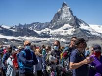 Touristen mit Mundschutz warten vor dem Matterhorn auf den Zug der Gornergratbahn.