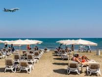 Reiserecht: Touristen am Strand von Larnaca, Zypern, beobachten die Landung eines Passagierflugzeugs