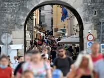 Touristen laufen durch die Altstadt von Zadar.