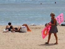 Eine Frau mit Mundschutz geht am Strand von Can Pastilla auf Mallorca.