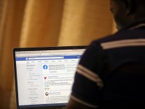 FILE PHOTO: Man opens the Facebook page on his computer to fact check coronavirus disease (COVID-19) information, in Abuja