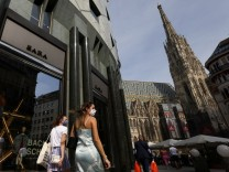 Women wearing protective face masks walk in front of St. Stephen's Cathedral in Vienna
