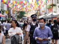 People walk through the Chinatown area, amid the coronavirus disease (COVID-19) outbreak, in London