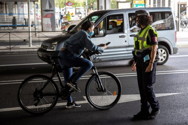 A police officer demands a cyclist for her safe conduct to leave the neighborhood of Vallecas in Madrid, Spain, 23 Septe
