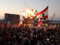Anti-government demonstrators take pictures of a metal sculpture spelling out the word 'revolution' topped by flames during a protest as Lebanese mark one year since the start of nation-wide protests, near Beirut's port