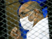 FILE PHOTO: Sudan's ousted President Omar al-Bashir is seen inside the defendant's cage during his and some of his former allies trial over the 1989 military coup that brought the autocrat to power in 1989, at a courthouse in Khartoum