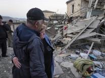 Zwei Einheimische stehen vor den Trümmern ihres Hauses in Aserbaidschan.