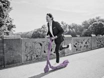 Businessman with e-scooter on a bridge model released Symbolfoto PUBLICATIONxINxGERxSUIxAUTxHUNxONLY JLOF00385