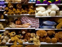 Man sleeping on a shelf between soft toys in a supermarket