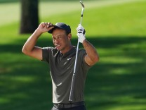 Tiger Woods takes off his hat after he hits out of a bunker on the second hole in the first round of the 2020 Masters g