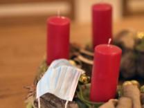 24.11.2020, Symbolbild, Adventskranz mit Mund-Nasenschutz-Maske im Wohnzimmer, Thema: Kontaktverbote und Ausgangsbeschr