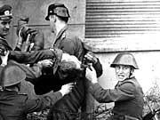 DDR-Grenzposten tragen in Berlin den leblosen Körper von Peter Fechter weg, nachdem er zuvor bei einem Fluchtversuch von DDR-Volkspolizisten niedergeschossen worden war (Archivfoto vom 17.08.1962).