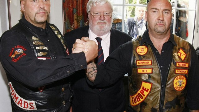 Lawyer von Fromberg watches as Maczollek of MC Bandidos and Hanebuth of Hells Angels shake hands following news conference in Hannover