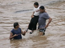 People try to cross the overflowing Huiza River at a damaged bridge in La Libertad