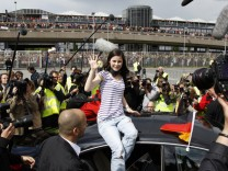 German singer Lena Mayer-Landrut is surrounded by the media as she waves to fans following her arrival at Hanover airport