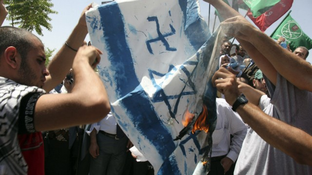 Jordanian protestors burn a banner with an image of a defaced Israeli flag during a demonstration outside the Jordanian prime ministry in Amman