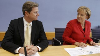 German Chancellor Merkel and Foreign Minister Westerwelle arrive for a news conference in Berlin