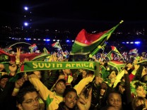 Fans raise scarves and wave flags during the opening concert for the 2010 World Cup at the Orlando Stadium in Soweto