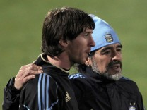 Argentina's coach Diego Maradona walks alongside Lionel Messi after a practice soccer session in Pretoria