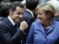 France's President Nicolas Sarkozy gestures beside German Chancellor Angela Merkel at the start of a European Union leaders summit in Brussels