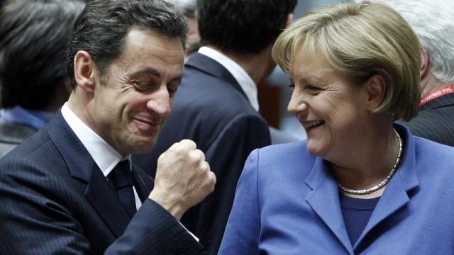 France's President Nicolas Sarkozy gestures beside German Chancellor Angela Merkel at the start of a European Union leaders summit in Brussels