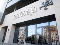 A man walks past a branch of Spanish savings bank Bancaja in Valencia