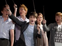 Daniel Radcliffe and members of the cast of Harry Potter wave their wands in Orlando, Florida