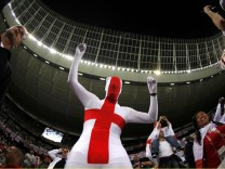 England fan wears an outfit featuring the cross of St George before the 2010 World Cup Group C soccer match against Algeria at Green Point stadium in Cape Town