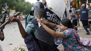 Rahela Akhter, a garment worker, tries to resist beating from the police during a protest in Dhaka