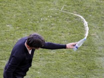 Germany's head coach Loew throws a bottle of water to the ground  during 2010 World Cup Group D soccer match against Serbia  in Port Elizabeth