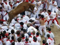 A fighting cow leaps over revellers during festivities in the bull ring during the San Fermin festival in Pamplona