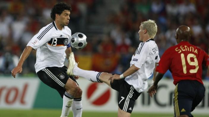 Germany's Schweinsteiger kicks ball in front of team mate Ballack during their Euro 2008 final against Spain in Vienna