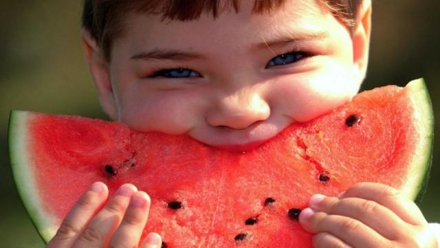 Junge isst eine Melone