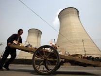 A street vendor pushes his cart of goods along a road in front of chimney stacks for a coal-burning power station in Beijing