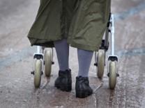 Ältere Frau mit Rollator auf matschiger Straße