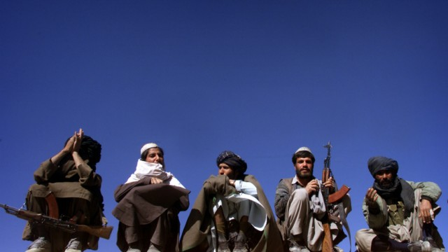 TALIBAN FIGHTERS SIT ON A WALL IN MAIDAN SHAHR