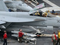 Members of the ground crew install missile onto a Super Hornet aircraft on the flight deck of the U.S. nuclear-powered aircraft carrier USS George Washington on the open seas east of South Korea