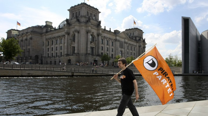 Member of Pirate Party walks in front of Reichstag as part of its campaign for September general election in Berlin