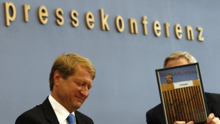 Outgoing government spokesman Wilhelm reacts as the head of the German federal press conference Goessling hands over a photograph as gift on his last news conference in Berlin