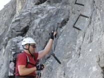 Klettersteig Uk : Gruppe junger bergsteiger auf einem steilen klettersteig mit